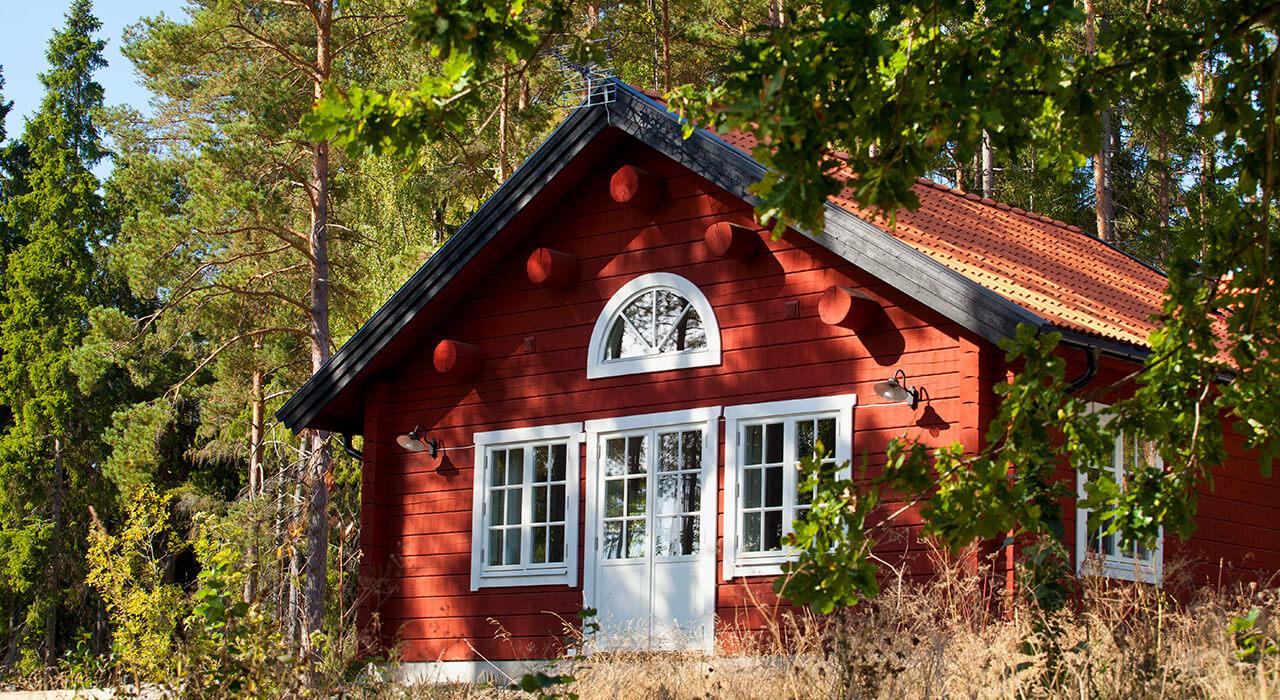 Vita fönster med spröjs på en röd stuga